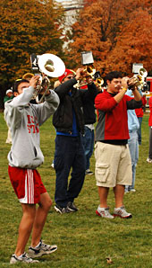 Marching band members rehearse on campus