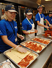 4-H'ers help assemble pans of lasagna for Special Olympics athletes.