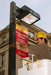 Worker installs banner on light pole