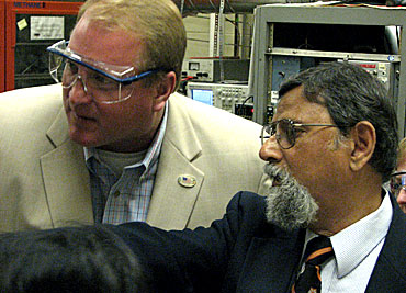 Iowa Gov. Chet Culver, left, examines a plasma reactor at Iowa State University's Microelectronics Research Center. Vikram Dalal, the director of the center, told the governor how plasma is used to fabricate thin film for solar cells.