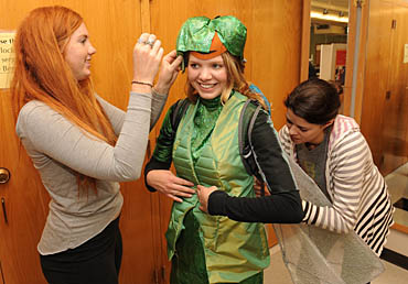 ISU apparel students Kaitlyn Clevenstine (left) and Marian Baggenstoss (right) apply the finishing touches to a dragonfly costume that will be worn by student dancer Laura Carr during the