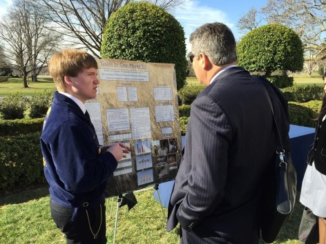 Iowa student shows off his research poster in the White House Rose Garden.