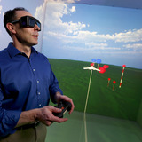 Eliot Winer operates the controls of Iowa State's C6 virtual reality room.