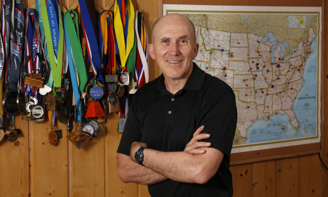 Dave Swenson with several of his medals and map of race locations