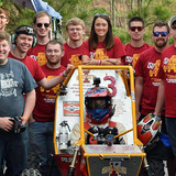 Members of the Iowa State Baja SAE Team around their off-road racer.