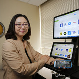 Su Jung Kim in her office with laptop and mobile phone