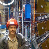 Jim Cochran stands in front of the ATLAS Detector in Europe.