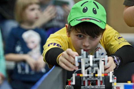 A student lines up his team's robot during FIRST LEGO League competition.