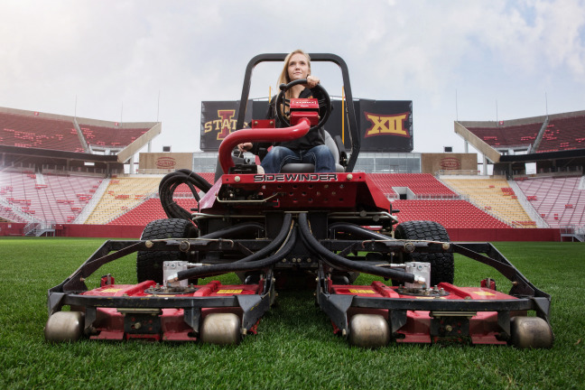 Georgeanna Heitshusen rides a lawnmower at Jack Trice Stadium