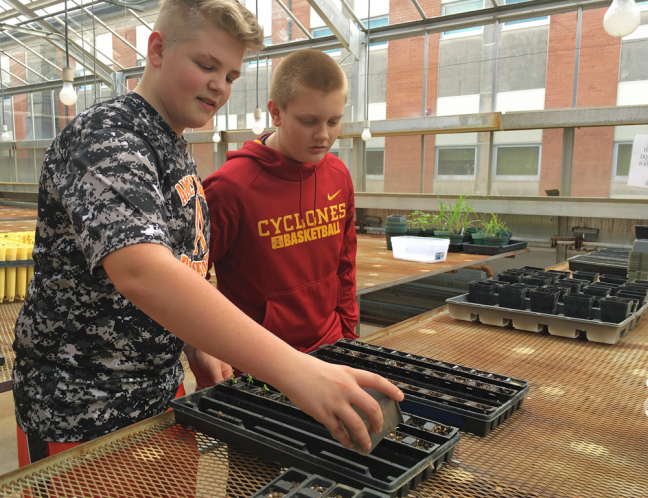 Ames High students Jake Schmit and Scott Junck work on a greenhouse experiment.