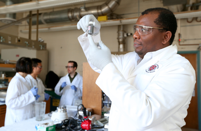 Martin Thuo in his lab with a vial containing liquid-metal particles