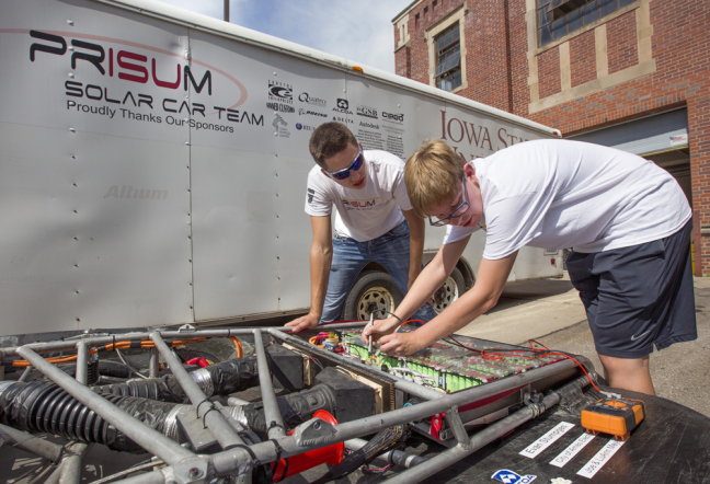 Team PrISUm members check their solar car's battery pack.