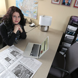 Raluca Cozma at desk with laptop and newspaper