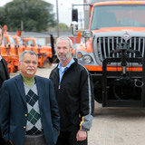 Iowa State researchers and DOT fleet manager stand near snow plow trucks