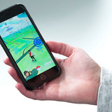 Hand holding phone displaying Pokemon GO game
