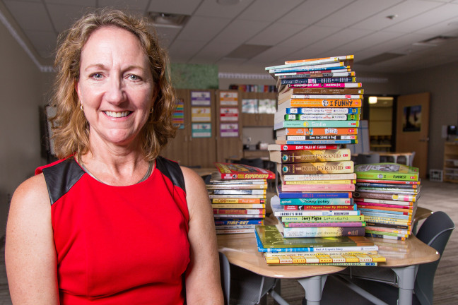 Emily Hayden in a classroom with stacks of books