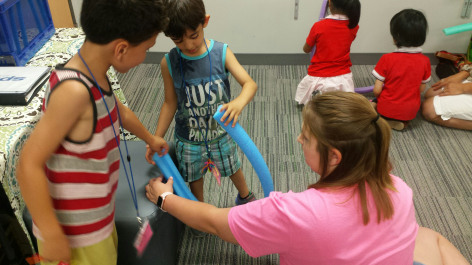 Students testing idea for a roller coaster made from a pool noodle