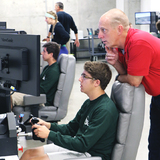 Retired astronaut Clayton Anderson works with a student during this year's Spaceflight Operations Workshop.