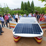 A crowd takes a close look at Penumbra, Team PrISUm's latest solar vehicle