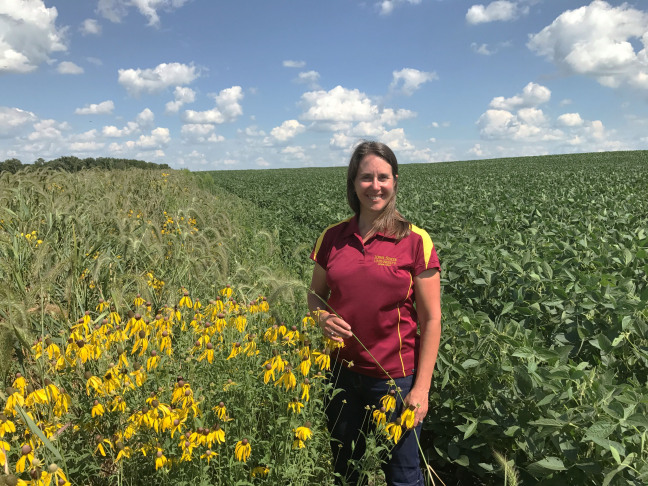 Lisa Schulte Moore stands in a farm field with prairie strips