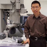 Xiaoli Tan with special specimen holder and a tramsmission electron microscope.