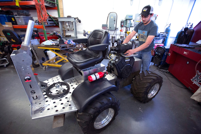 James McCormick works on a quarter-scale tractor in a workshop