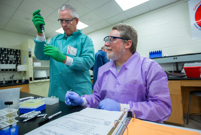 Teachers work together on DNA analysis in lab