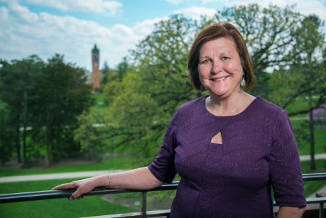 Dianne Bystrom standing on Catt Hall balcony with Campanile in background
