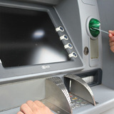 Person inserting debit card in ATM