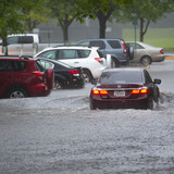 Car driving through a flooded parking lot