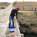 A scientist lowers a water sampling device off of a bridge into a rural stream