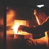 Paul Canfield removes a sample from a flux-growth furnace.