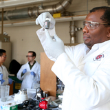 Martin Thuo in his lab with liquid-metal particles that make heat-free solder possible