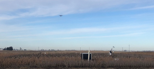 A drone aircraft hovering above a farm field