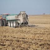 Tractor and farm equipment applying manure to a farm field