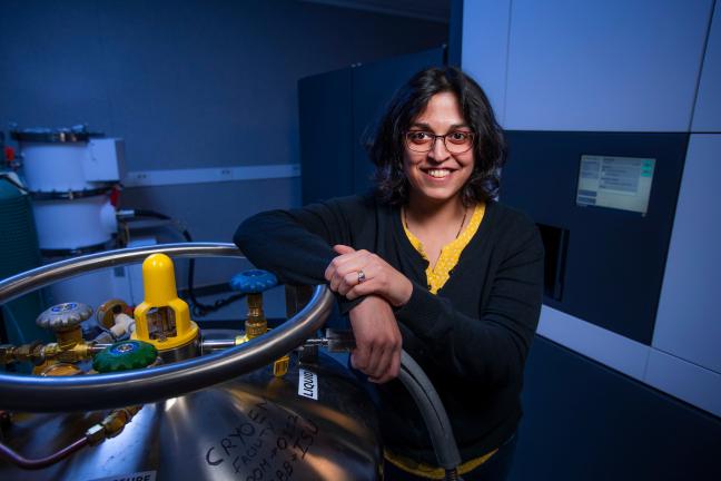 Dipa Sashital leans against scientific equipment in a laboratory in the ISU Molecular Biology building