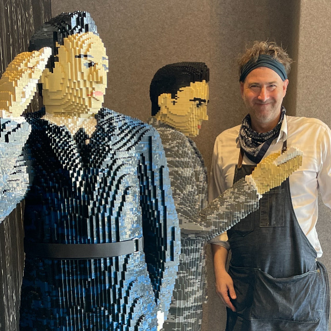Chris Ihle stands next to completed LEGO build