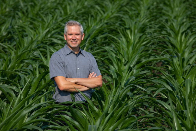 Matthew Hufford stands by himself in a corn field